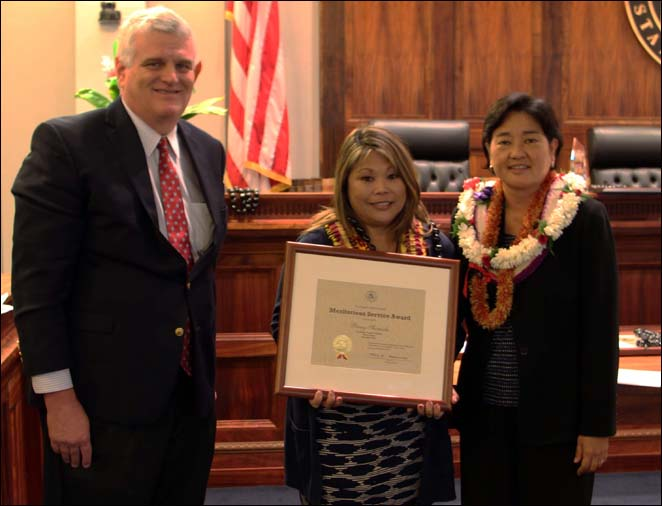 Chief Justice Mark Recktenwald (left) and Associate Judge Lisa Ginoza (right) confer the Judiciary's  Meritorious Service Award to Penny Shimada, Court Operations and Support, Family Court, Second Circuit (center)