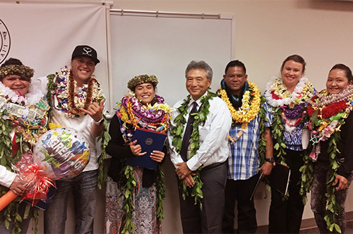 Hilo Drug Court Judge Greg Nakamura stands in the center of a group of six Big Island Drug Court graduates, all wearing leis, May19, 2016.