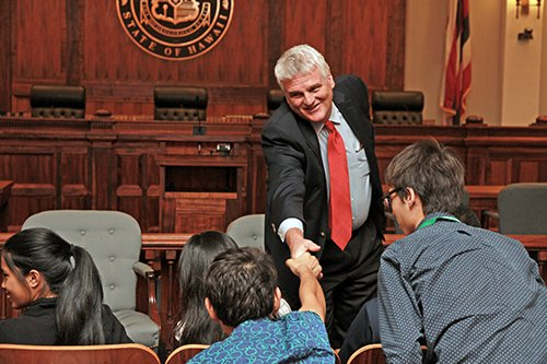 """Chief Justice Mark Recktenwald in the Supreme Court courtroom shaking hands with a high school student from the University of Hawaii's """"Law and Justice Summer Program."""""""