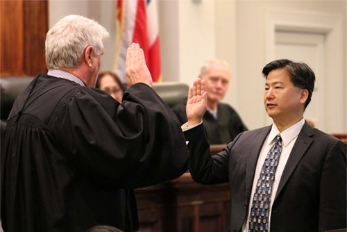 Chief Justice Recktenwald adinisters the oath of office to James Kawashima.