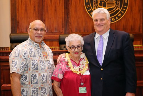 Administrative Director of the Courts Rod Maile, Volunteer Millie Botelho, and Chief Justice Mark Recktenwald in front of the bench of the Supreme Court courtroom.