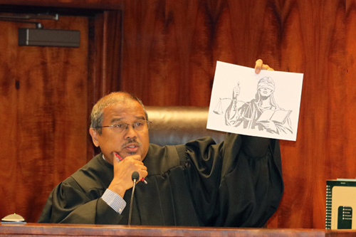 Oahu Judge William Domingo shows a sketch of Lady Justice to 8th grade students who visited his courtroom at the First Circuit Court Building on March 7, 2017. Judge Domingo used the sketch to explain the Judiciary's role in applying the rule of law equally for all people.