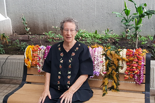 Photograph of Jan Dapitan sitting on a bench dedicated in her behalf for the role she played in establishing Hawaii's Environmental Court. The top of the bench is covered with leis.