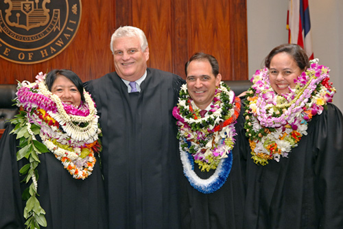 Photograph of Chief Justice Mark E. Recktenwald being photographed with new judges Darolyn Lendio Heim, Brian Costa and Trish Morikawa.
