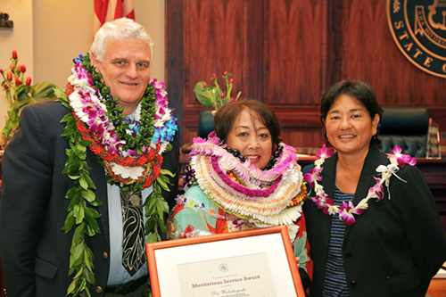 Chief Justice Mark E. Recktenwald and Associate Judge Lisa Ginoza present an award to a Judiciary employee.