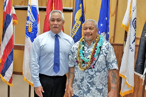 Judge Melvin Fujino standing with Big Island Veterans Treatment Court's 11th graduate in the Kona courtroom, military flags behind them, 11/05/2018.