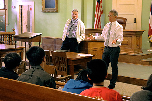 Photographs of First Circuit Judges James C. McWhinnie (left) and James H. Ashford as they speak to middle school students.