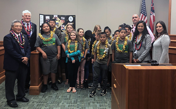 "Photo of Congratulating the proud students are (left) Third Circuit Chief Judge Greg Nakamura and Chief Justice Mark E. Recktenwald and (right) Third Circuit District Family Court Judge Darien Nagata (wearing lei), Counselor Krissy Bajo, and (back right) Chad ""Keone"" Farias, Complex Area Superintendent."