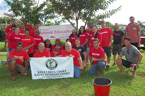 "A group of volunteers pose with a ""Kauai Drug Court, Kauai Veterans Treatment Court"" sign at the Kauai Animal Education Center on July 26, 2019."
