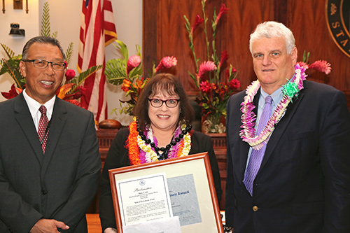 Mary Cook, Clerk IV, Juvenile Client Services Branch, Specialized Services Section, Kids First, First Circuit (Oahu) Family Court - Kapolei, with Intermediate Court of Appeals Associate Judge Derrick H.M. Chan and Hawaii Supreme Court Chief Justice Mark E. Recktenwald, in the Supreme Court courtroom, 09/30/2019.