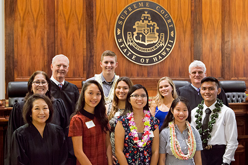 Front left: Hawaii Supreme Court Associate Justice Paula A. Nakayama, Konawaena High School student Tyra Bailey, Waipahu High School student Grace Chinen, Roosevelt High School student Michelle Phan. Middle left: Associate Justice Sabrina S. McKenna, Kamehameha Schools – Kapalama student Maia Motta, King Kekaulike High School student Natalie Dzubian, Kapaa High School student Kyler Arruda-Sukehira. Back left: Associate Justice Michael D. Wilson, Christian Liberty Academy student Cameron Wells, Chief Justice Mark E. Recktenwald, all standing in front of the bench of the Hawaii Supreme Court courtroom at the annual Pro Bono Celebration, 10/24/2019.