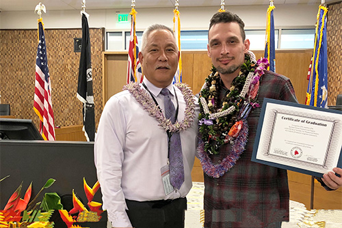 Judge Melvin Fujino with the Big Island Veterans Treatment Court's 15th graduate, in a courtroom at the new Keahuolu Courthouse in Kona.
