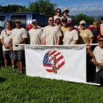 First Circuit Judge Edward Kubo, Jr., and Third Circuit Judge Henry Nakamoto with Veterans Treatment Court associates standing outside on a sunny blue-sky day, on a lawn with a Big Island Veterans Treatment Court banner at the Hilo Veterans Day Parade, 11/09/19.