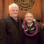 Chief Justice Mark E. Recktenwald and Associate Judge Clyde J. Wadsworth stand in front of the Hawaii Supreme Court courtroom bench after Wadsworth's swearing in ceremony, 11/12/19.