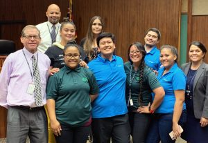 Photo of: Front row (left): District Family Court Judge Lloyd Poelman, Samantha Uu, Jason Gumbac, Sharla Fujimoto, Aponi Boyer, and District Family Court Judge Adrianne Heely. Second row (left): Ipolani Mae-Pescaia, Malia Ferriera, and Kholby Akuna. Back: Brian Raphael.