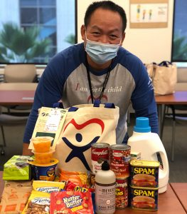 Amphay Champathong, Supervisor of the Judiciary's Court Appointed Special Advocates (CASA) Program, stands at a table stacked with packaged food and other items included in the care bags for foster families.