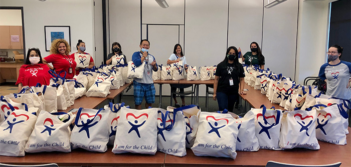 Nine CASA staff members in a large room stand beside tables stacked with CASA care bags, May 2020.