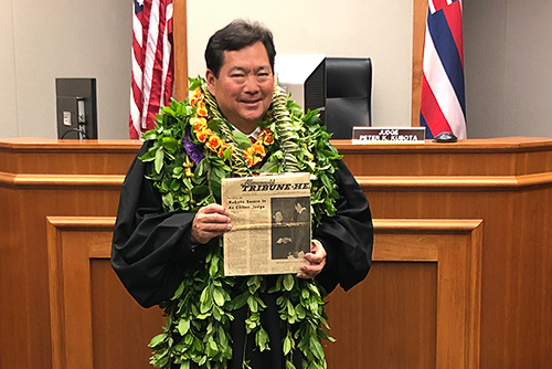 Third Circuit Court Judge Peter K. Kubota stands in front of his courtroom bench holding a copy of the 04/17/1974 edition of the Hawaii Tribune-Herald newspaper.