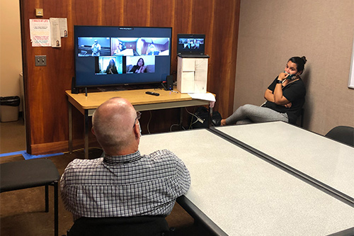 Counselor Stephen Holbrook and Probation Officer Ana Ochoa wearing masks and sitting more than six feet apart in a room watching the 72nd Drug Court Graduation proceedings on a television showing the video feeds of people participating remotely from different locations.