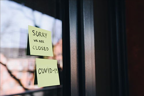 "Two post-it notes on a glass door. One says, ""Sorry We Are Closed,"" the other, ""COVID-19."""