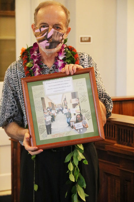 Justice Pollack holds the photo given to him by staff of the Hawaii Supreme Court. In the photo, the justices and staff members are social distancing and wearing masks.