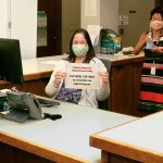 Librarian Marlene Cuenco and State Law Librarian Jenny R.F.F. Silbiger wearing masks and holding up hand sanitizer and the reservations phone number at the Hawaii Supreme Court Law Library reference desk, 08/03/2020.