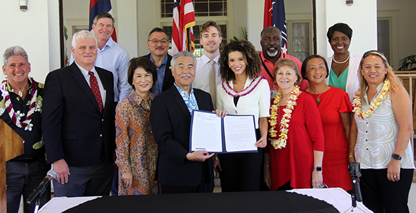 Photo of First row, left, David Lassner, Chief Justice Recktenwald, First Lady Dawn Amano Ige, Gov. David Ige, Samantha Neyland, Sen. Roz Baker, Sandy Ma, and Rep. Lynn DeCoite. Back row, left, Council Chair Tommy Waters, Rep. John Mizuno, Ty Trumbo, Alphonso Braggs, and Letitia Brown.