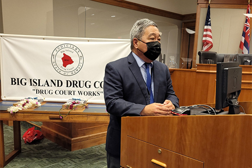 Third Circuit Chief Judge Robert Kim makes remarks from a courtroom podium at the Big Island Drug Court's 57th graduation ceremony, 08/05/2021.