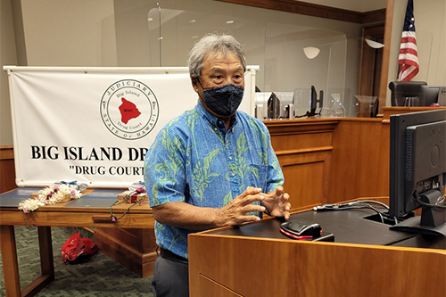 Retired Hilo Drug Court Judge Greg Nakamura makes remarks from a courtroom podium at the Big Island Drug Court's 57th graduation ceremony, 08/05/2021.