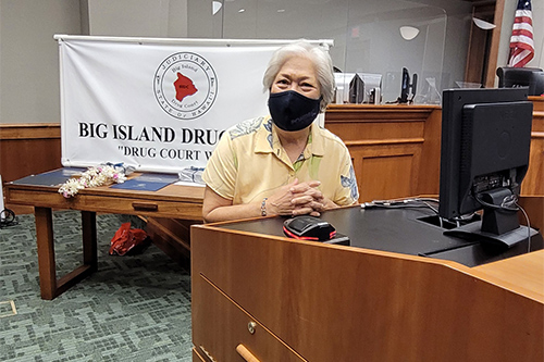 Friends of Big Island Drug Court Board member Debbie Maiava Ching, at a courtroom podium, shares her thoughts with attendees at the Big Island Drug Court's 57th graduation ceremony, 08/05/2021.