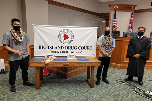 """In the courtroom, two graduates stand on the left and right sides of a table holding a Big Island Drug Court banner (""""Drug Court Works""""), with Hilo Drug Court Judge Henry Nakamoto on the far right, at the program's 57th graduation ceremony, 08/05/2021."""
