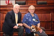 Chief Justice Mark Recktenwald pauses for a photo with volunteers Ron Stebbins, and the First Circuit's Veterans Treatment Court dog, Athena.
